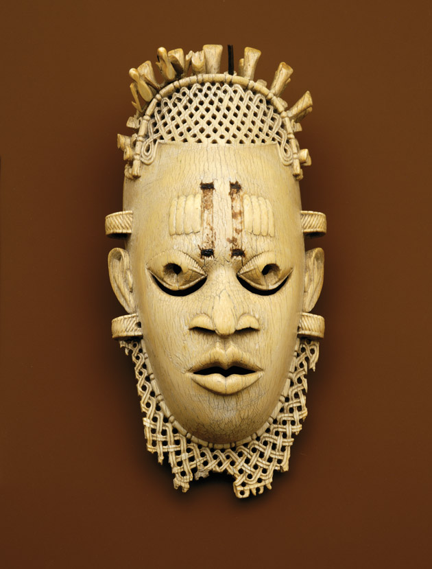 Image of a ivory mask depicting the face of a woman and carved with lattice-like detail surrounding her face
