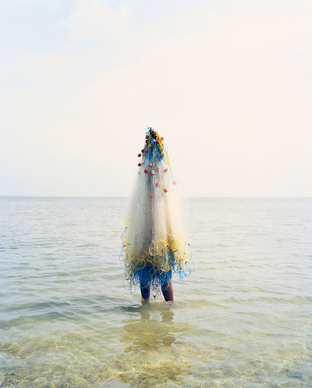 Photograph of a figure covered in fishing nets standing in shallow water