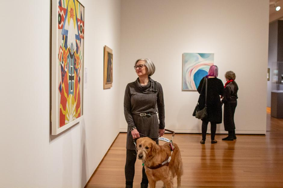 Photo of Art Beyond Sight tour participant looking at a colorful, abstract painting at the Seattle Art Museum with her guide dog.